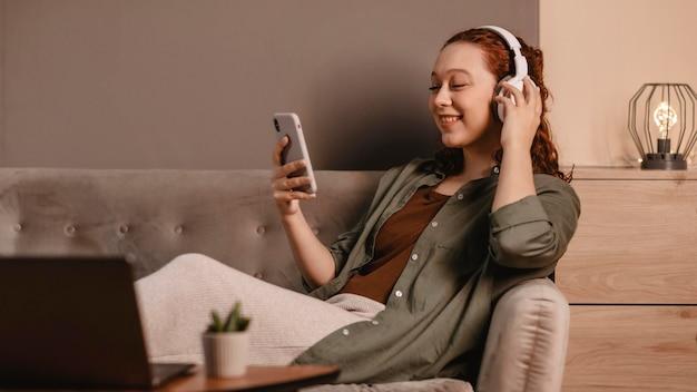 Женщина, использующая современные наушники и смартфон на диване у себя дома