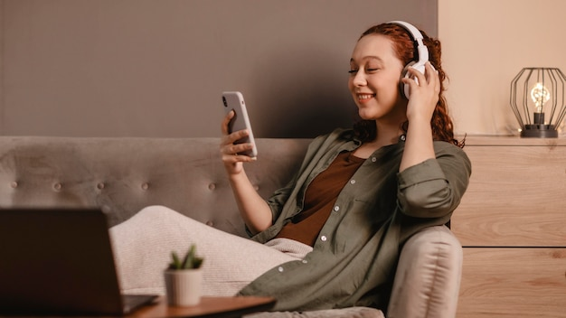 Woman using modern headphones and smartphone on the sofa at home