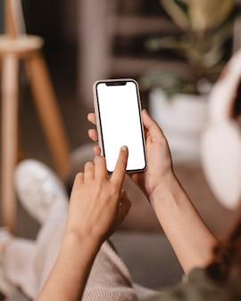 Donna che utilizza smartphone e cuffie moderne a casa