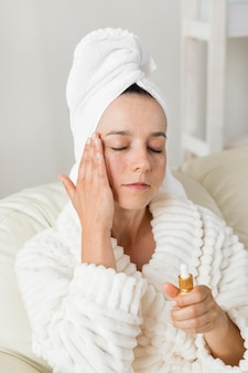 Woman using moisturizer for her skin and wearing a bathrobe