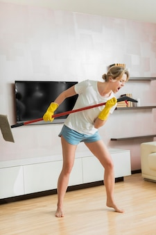 Woman using the mop as a microphone long view