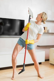 Woman using the mop as a microphone