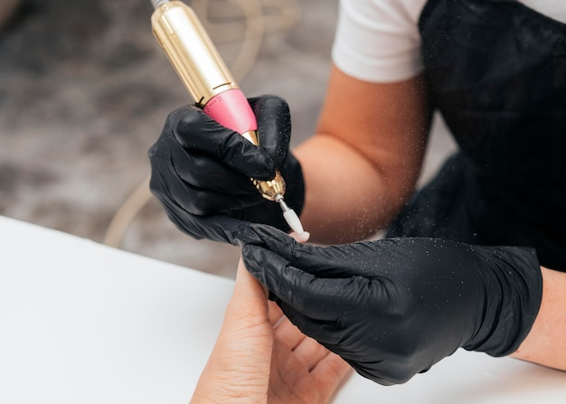 Woman using a nail file on client and wearing gloves