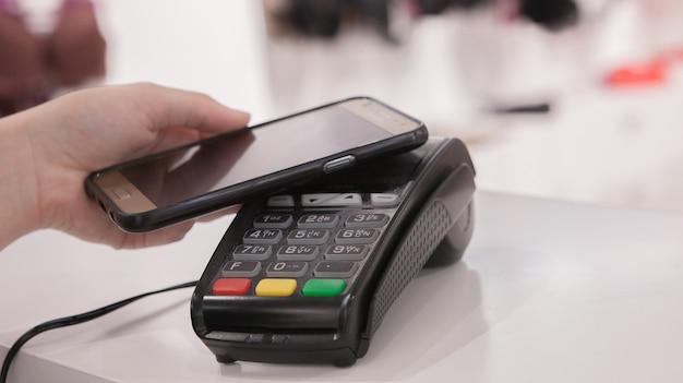 Женщина, использующая технологию nfc для оплаты в магазине