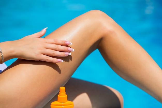太陽の紫外線から足の保護を日焼けオイルスプレーを使用している女性