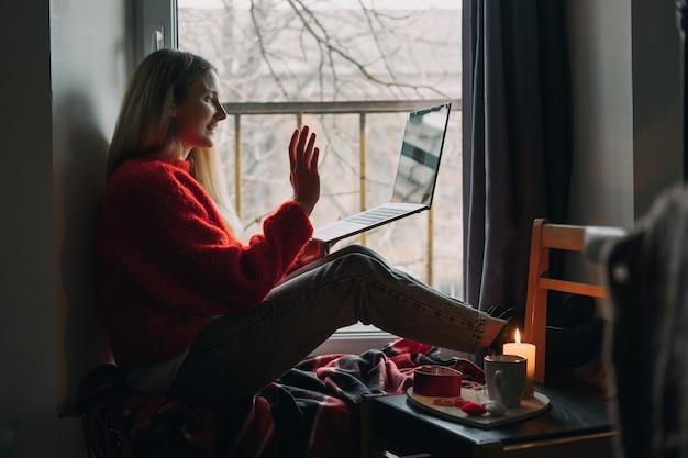 Женщина, использующая приложение онлайн-знакомств на ноутбуке. день святого валентина, свидания, встречи во время вспышки коронавируса. любовь на расстоянии во времена коронавируса.