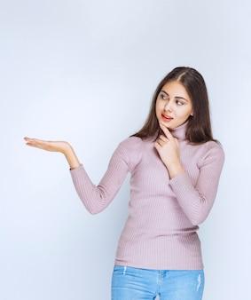 Donna che usa la mano aperta per presentare qualcosa o dare una spiegazione.