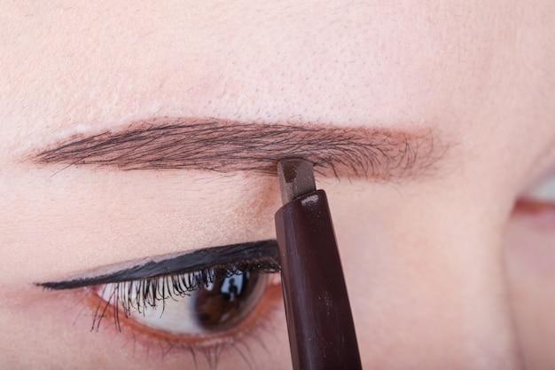 Woman using pencil makeup eyebrow