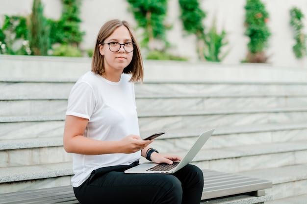 여자 프리랜서 작업 야외 전화 및 노트북 사용