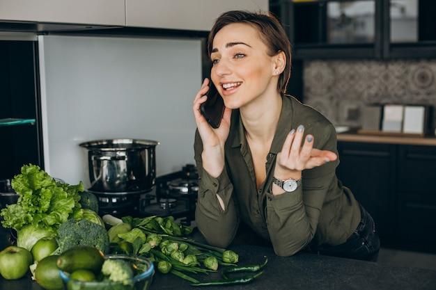 여자는 부엌에서 전화를 사용하고 녹색 채소에서 식사를 요리
