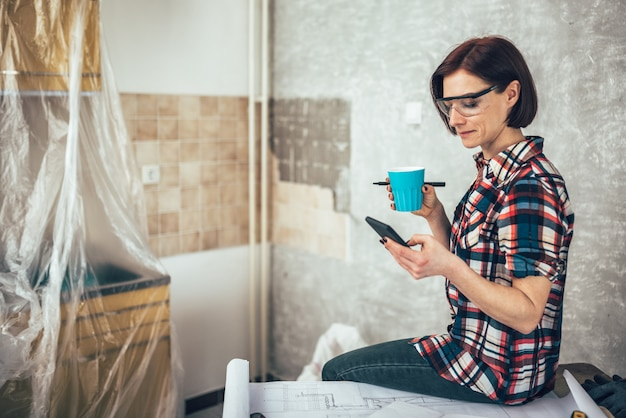 Woman using phone and drinking coffee while renovating kitchen