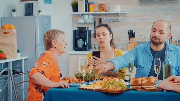 Woman using phone during dinner showing some pictures to her mother. multi generation, four people, two happy couples talking and eating during a gourmet meal, enjoying time at home.