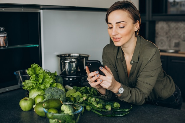 Woman using phone at the kitchen and cooking meal out of green veggies