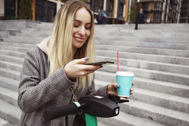 임대 전자 스쿠터에 전화 모바일 앱을 사용하는 여자