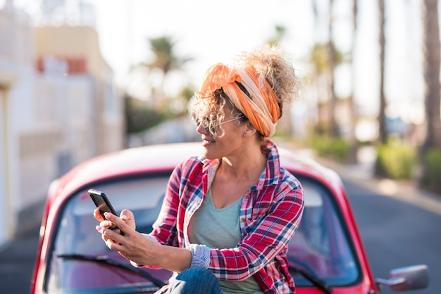 女性ドライバーのための実際の旅行や夏休み休暇の車で屋外の電話を使用している女性