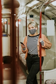 Woman using a phone on a train in the new normal