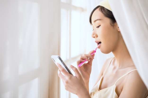 Woman using a phone while brushing her teeth