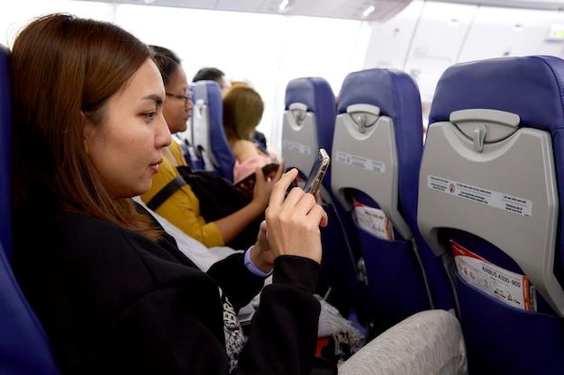 飛行機で旅行中に携帯電話を使用して女性