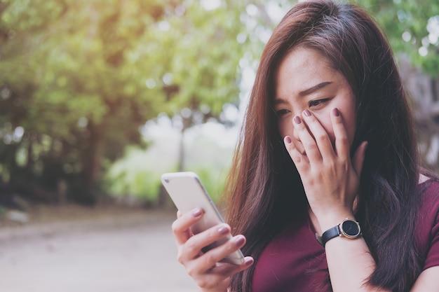 Женщина, используя телефон с чувством грустно