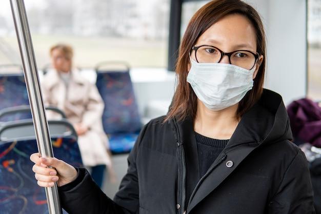 サージカルマスクと公共交通機関を使用して女性