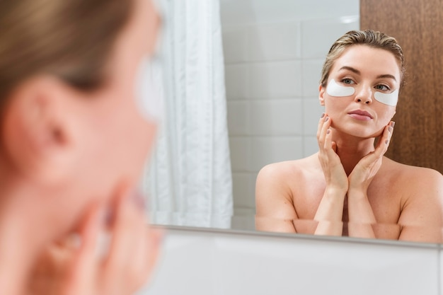 Woman using reducing dark circles patches in the bathroom