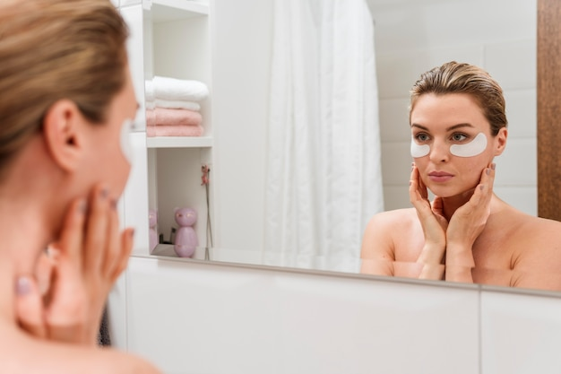 Woman using reducing dark circles patches in the mirror
