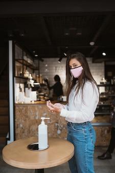 消毒ジェルを使用している女性は、カフェでコロナウイルスウイルスの手をきれいにします。