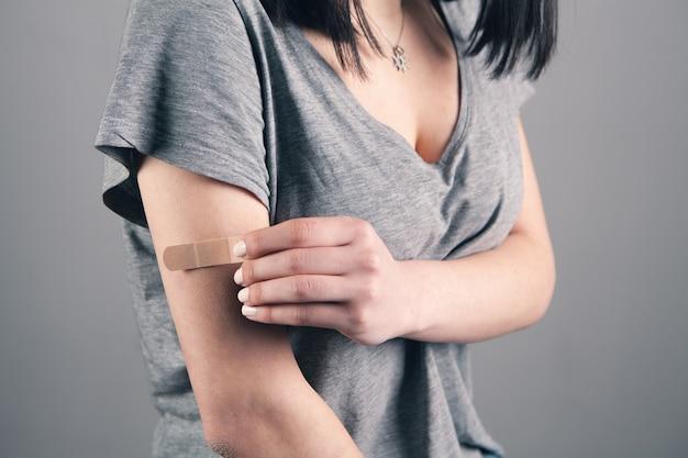 다친 팔에 스카치 테이프를 사용하는 여성