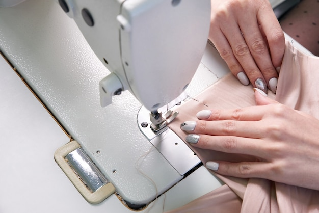 Woman using a sewing machine in tailor studio