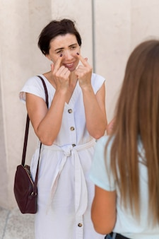 Woman using sign language to convey crying to her friend