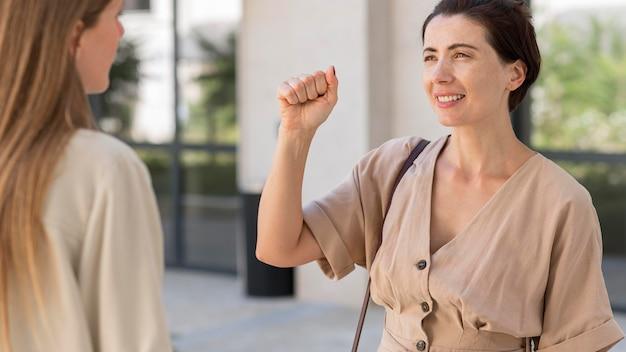 Женщина с помощью языка жестов разговаривает со своим другом