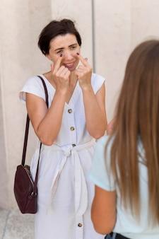 友達に泣き声を伝えるために手話を使う女性