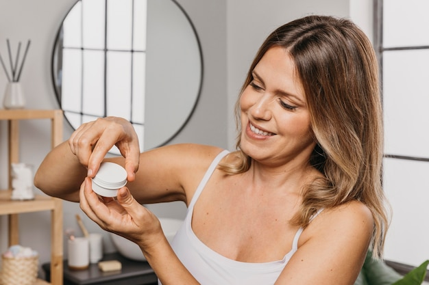 Woman using a skin care product without label