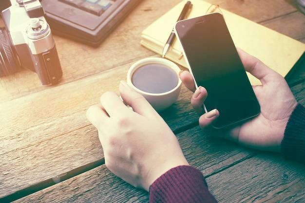 作業台でスマートフォンとコーヒーカップを使用している女性