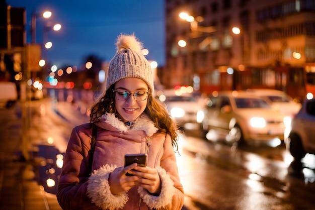 도시에서 밤에 스마트 휴대 전화를 사용하는 여자.