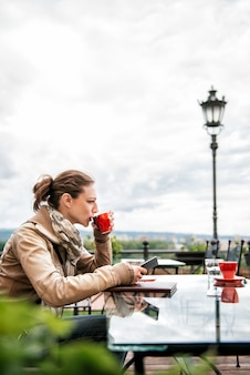 Woman using smart phone and drinking coffee