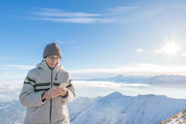 Woman using smart phone on the mountains.