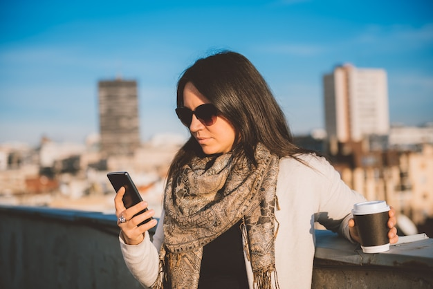 Woman using smart phone on the rooftop