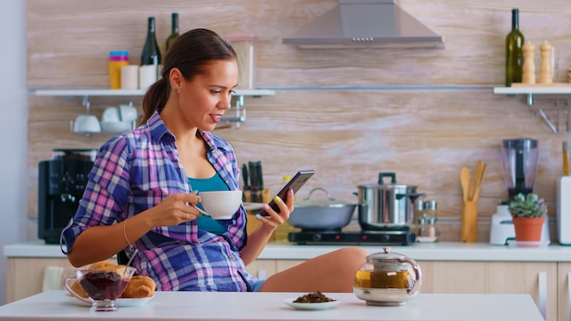 Woman using smart phone for social media and during breakfast drinking a cup of green tea in kitchen. holding phone device with touchscreen using internet technology scrolling, searching on gadget