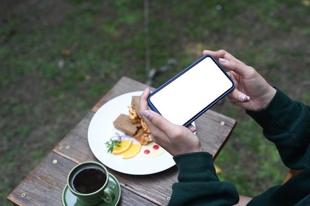 写真を撮るスマートフォンを使用している女性