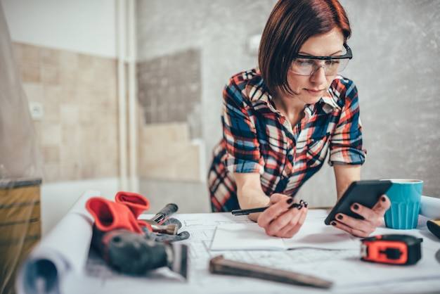 Woman using smart phone while renovating kitchen