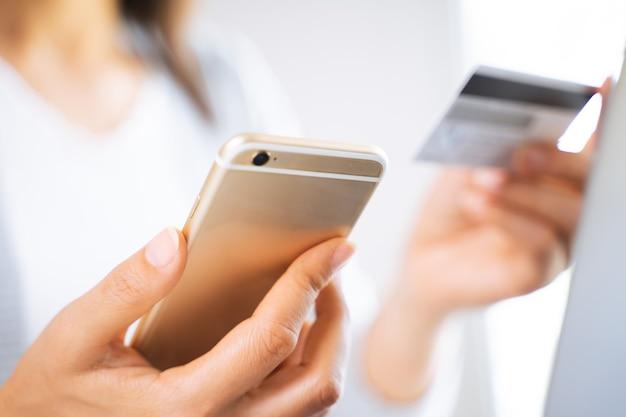 Женщина с помощью смартфона с помощью кредитной карты. интернет-магазины, финансы, интернет-реклама.