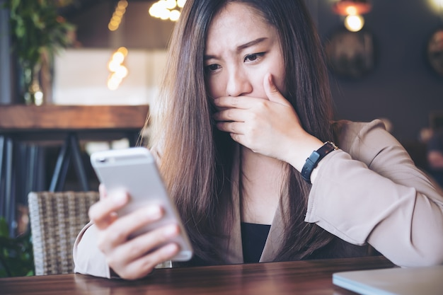 Woman using smart phone with feeling frightened