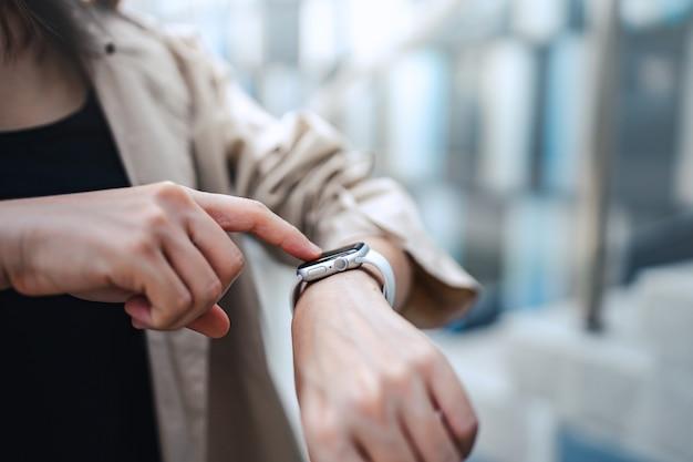 건강 응용 프로그램을 통해 맥박을 확인하는 스마트 시계를 사용하는 여성