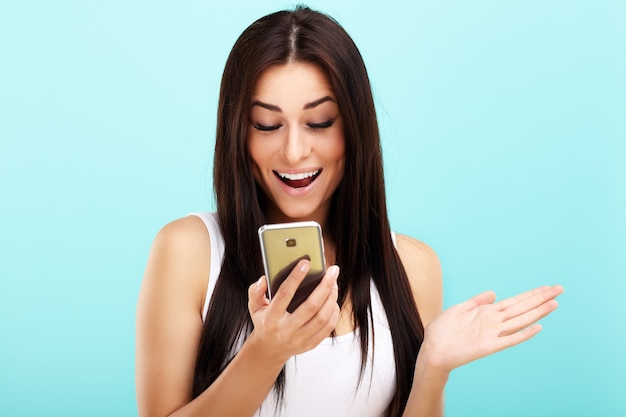 Woman using smartphone against blue background