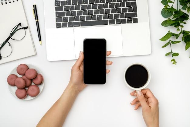スマートフォンを使用して、オフィスでコーヒーを飲む女性