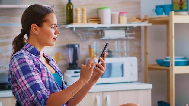 スマートフォンを使用して緑茶を飲む女性は、キッチンで自由な時間を過ごします。朝食時にインターネット技術を使用したタッチスクリーン付きの電話デバイスのスクロール、ブラウジング、ガジェットの検索