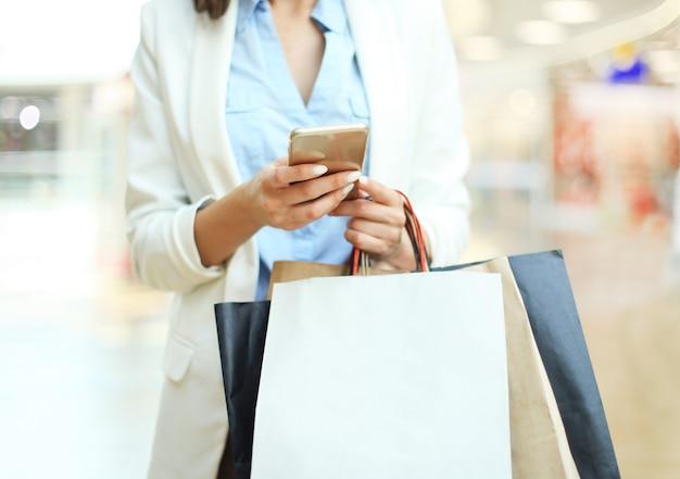 스마트폰을 사용하고 쇼핑몰 배경에 서 있는 동안 쇼핑백을 들고 있는 여자.