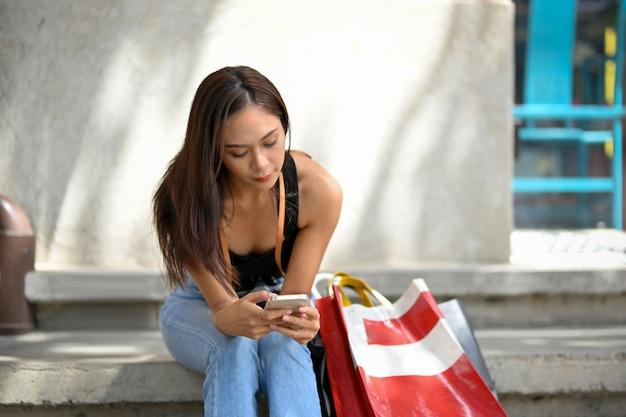 プレゼントを購入した後、スマートフォンを使用して外の階段に座っている女性