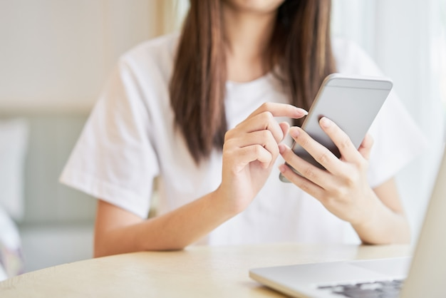 Woman using smartphone for the application on table in room.